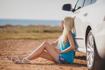Beautiful young sexy woman near a car outdoor