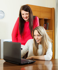 amazed women using laptop