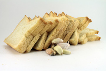 Sliced bread and garlic cloves. Isolated object on white backgro