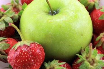 The background of the ripe strawberry and green Apple.