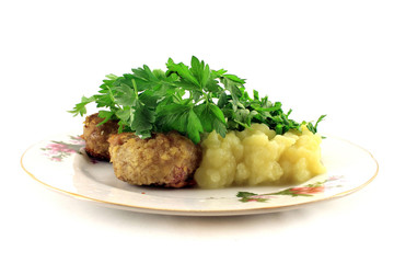 Mashed potatoes with cutlets and greens on the plate. Isolated o