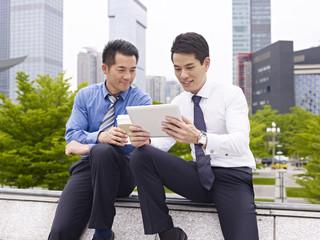 asian businesspeople using ipad outdoor