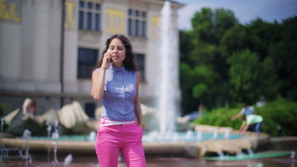 Woman walking next to the fountain and talking on the phone