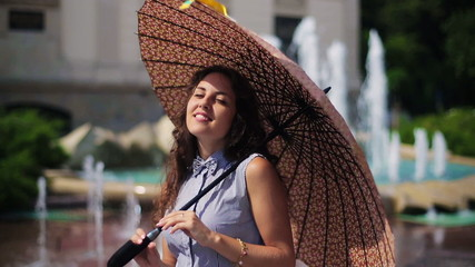 Shy woman smiling to the camera and holding brown umbrella