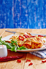 Enchiladas dish with red hot chilli with sour cream