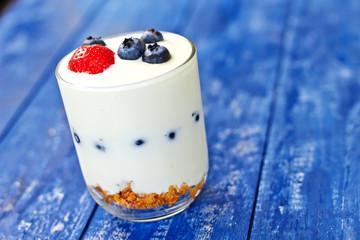 Yogurt glass with berries and musli on table
