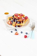 Golden waffles with berries and cup of honey wide