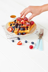 Hand adding berries on golden waffles with sugar and honey
