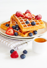 Golden waffles with berries and cup of honey