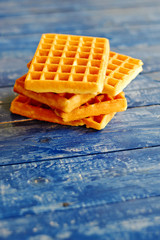 Golden waffles on vintage blue wooden table with space