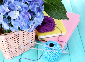 Hydrangea with books and threads on table close-up