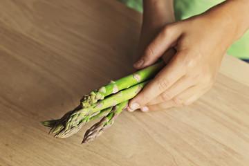 Esparagos verde sujetos en manos de niño