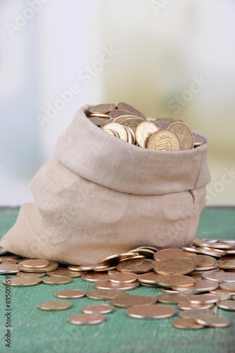 Poster Fabric bag full of Ukrainian coins on wooden background