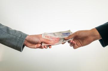 Businessmen exchanging british money pounds sterling