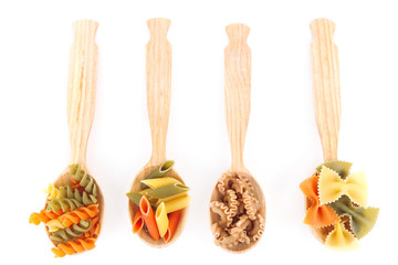 Assortment of colorful pasta in wooden spoons isolated on white
