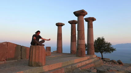 man meditating in the temple at sunset, yoga