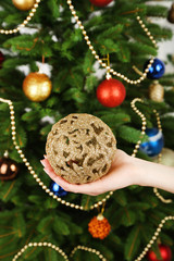 Christmas ball in hand on Christmas tree background