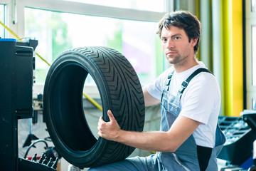 Mechaniker bei Reifenwechsel in Autowerkstatt