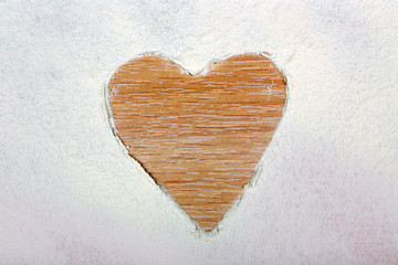 Heart figure made of sugar powder on wooden background