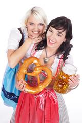 Zwei junge Frauen in Tracht mit Bier und Brezel