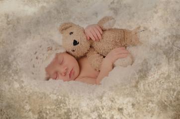 Newborn kuschelt mit Bärchen