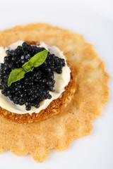 Black caviar with crispy bread on plate closeup