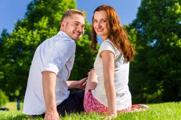 Couple sitting on park lawn enjoying sun