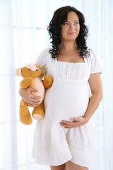 Young pregnant woman with teddy bear on light background