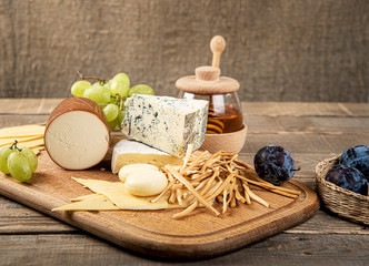 Various types of cheese, grapes, honey composition