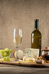Various types of cheese, grapes, honey,  bottle of wine  composi