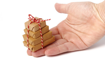 Tiny pile of gifts on hand palm - isolated