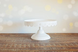 Cake plate on vintage wooden table over bokeh background