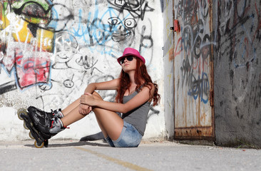 sitting girl with roller skates on graffiti background