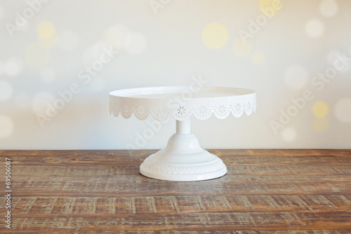 Leinwandbild Motiv Cake plate on vintage wooden table over bokeh background