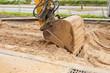 Strassenbauarbeiten mit einer grossen Baggerschaufel