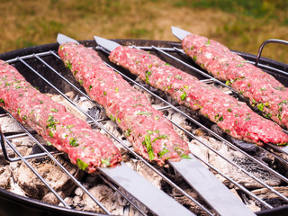 Shish kebab prepared over a black round shaped charcoal barbecue