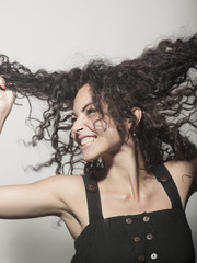 beautiful cheerful woman holding a curly hair