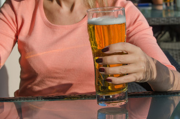 Hand of woman holding a glass of beer