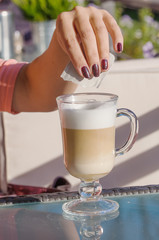 Hand of woman putting sugar in a glass of coffee