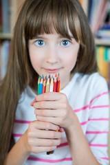Beautyful girl holding many pencils.
