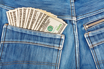 A hundred dollar bills sticking in the back pocket of denim blue