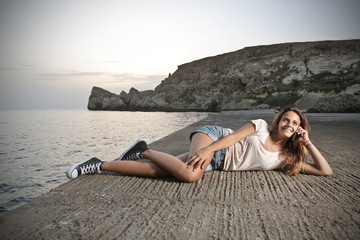 young casual girl who is lying on a pier