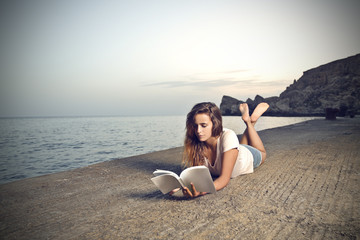 young girl who is  lying on a pier and is reading a book