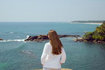 The girl looks in the ocean