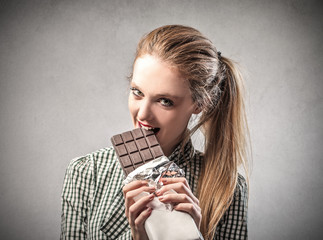 beautiful woman is eating a chocolate bar