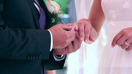 Male and female hands clasp in a wedding ceremony