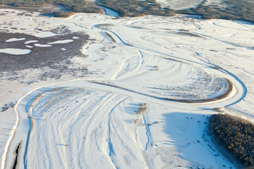 Snow covered plain with river, top view