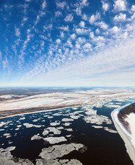 Great river with floating ice floes, top view