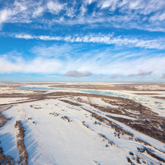 Snowy fields of the countryside with river in early spring, top