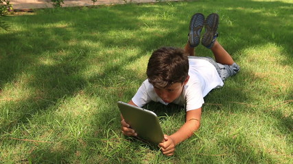 little cute kid leisure time with digital tablet in park